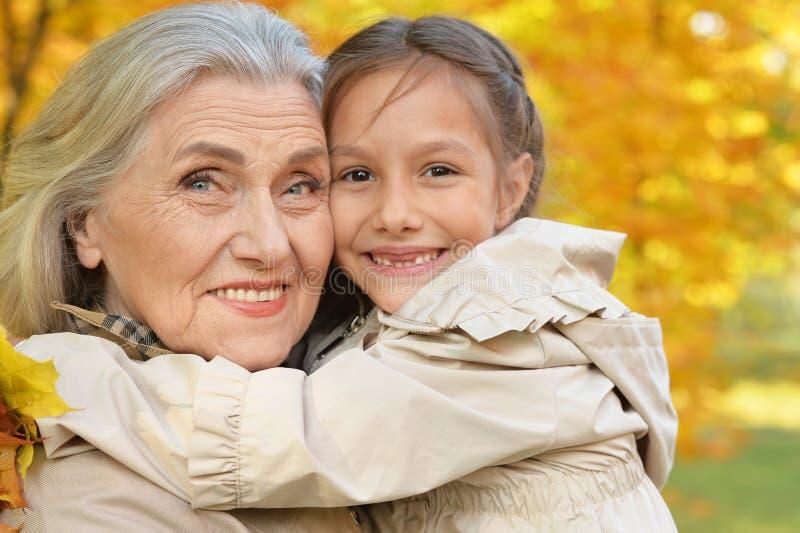 Retrato de la abuela y de la nieta que abrazan al aire libre foto de archivo