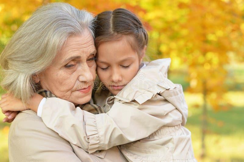 Retrato de la abuela y de la nieta tristes en parque imagenes de archivo
