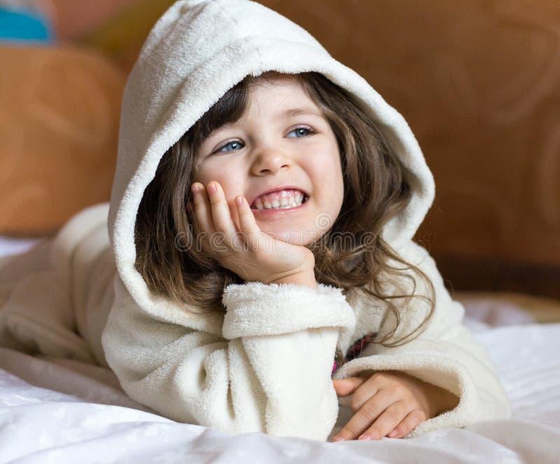 Retrato de la albornoz que lleva de la niña adorable que sonríe después de bañar foto de archivo libre de regalías