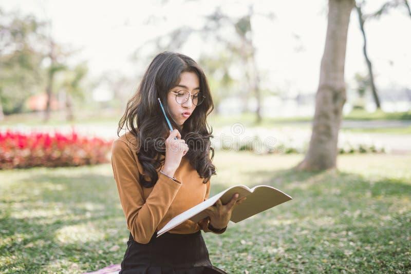 Retrato de la alta colegiala que piensa y leído un libro en parque, libro de lectura de la educación y concepto creativo de pensa foto de archivo libre de regalías