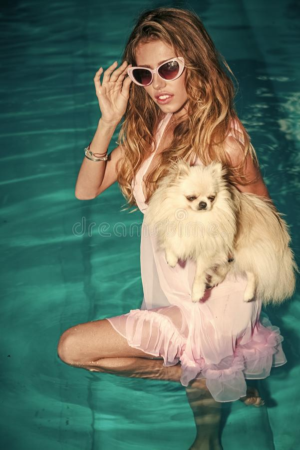 Retrato de la alta moda de la mujer elegante Mujer sensual con el perrito lindo del perro de Pomerania en agua azul foto de archivo libre de regalías