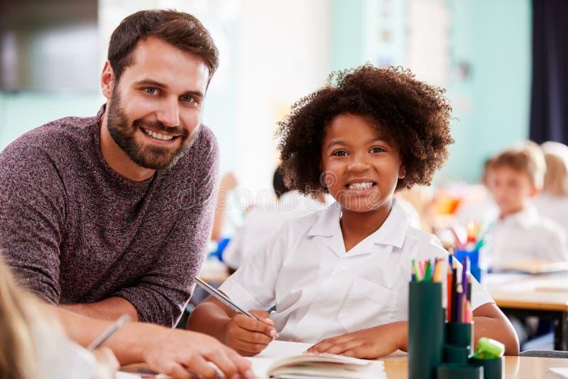 Retrato de la ayuda del uniforme uno a uno de Giving Female Pupil del profesor de escuela que lleva elemental de sexo masculino foto de archivo libre de regalías