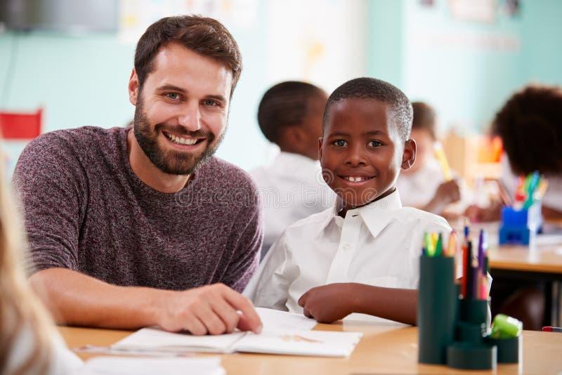 Retrato de la ayuda del uniforme uno a uno de Giving Male Pupil del profesor de escuela que lleva elemental en clase foto de archivo libre de regalías