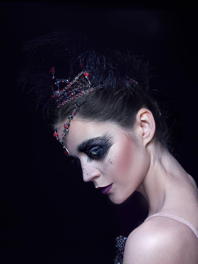 Retrato de la bailarina en el papel de un cisne negro en fondo negro imágenes de archivo libres de regalías