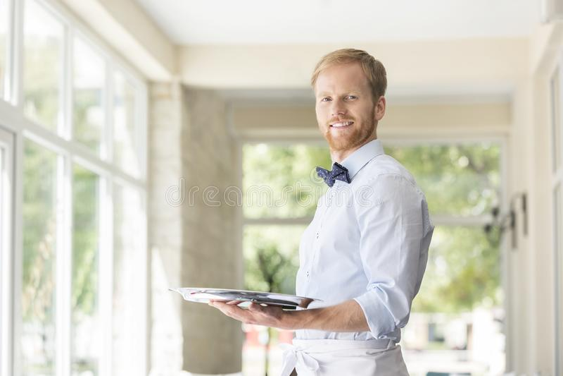 Retrato de la bandeja joven confiada de la tenencia del camarero mientras que se coloca en el restaurante imagen de archivo