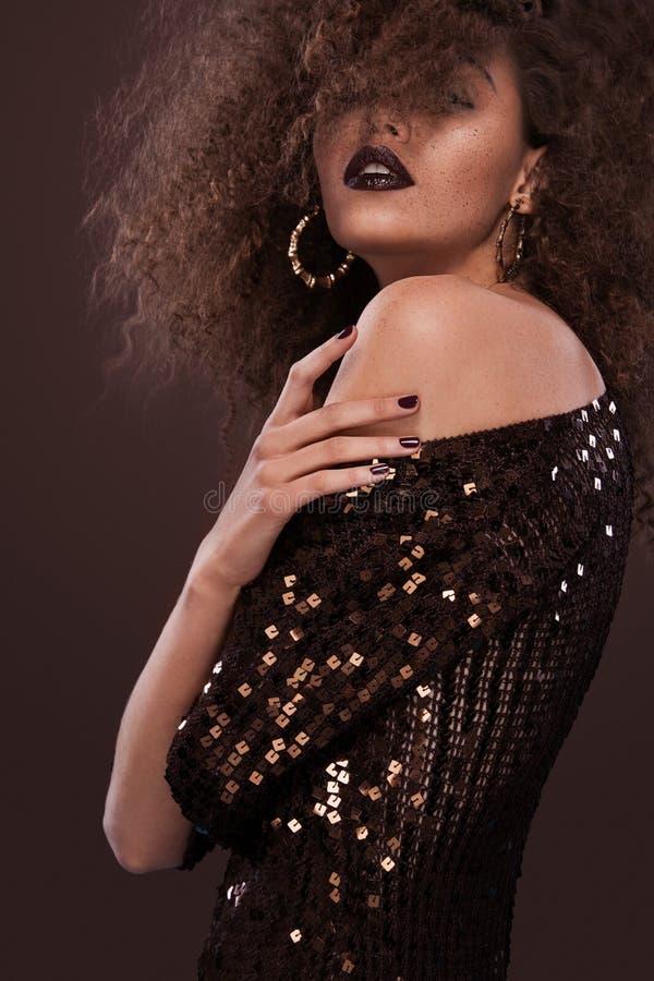 Retrato de la belleza de la muchacha con el peinado afro Muchacha que presenta en fondo marrón Tiro del estudio fotos de archivo