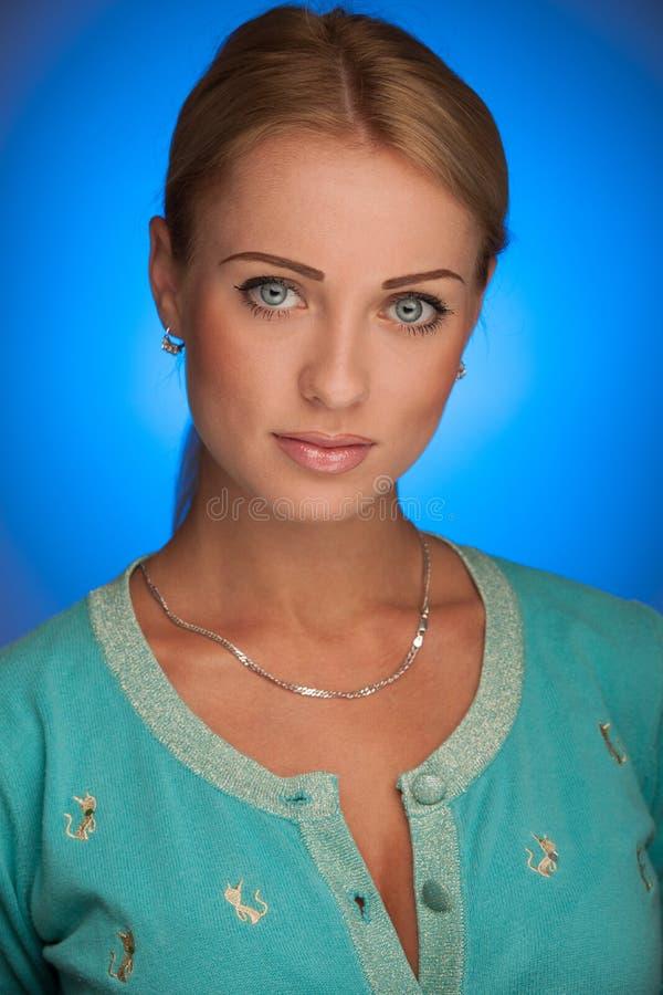 Retrato de la belleza de la mujer joven atractiva con de la aureola la parte posterior azul adentro imagen de archivo