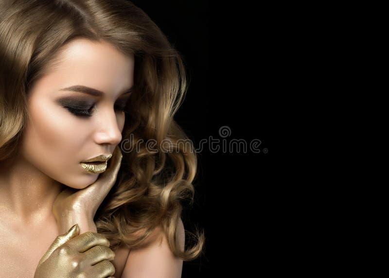 Retrato de la belleza de la mujer joven con maquillaje de oro foto de archivo