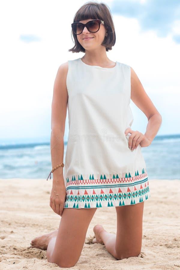Retrato de la belleza de la mujer morena atractiva en el vestido blanco en la playa con las gafas de sol Moda del verano de la tr fotos de archivo