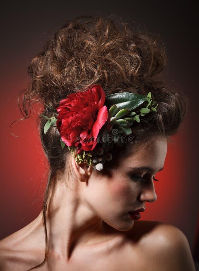 Retrato de la belleza de Stubio de la mujer joven atractiva con la peonía roja imagen de archivo