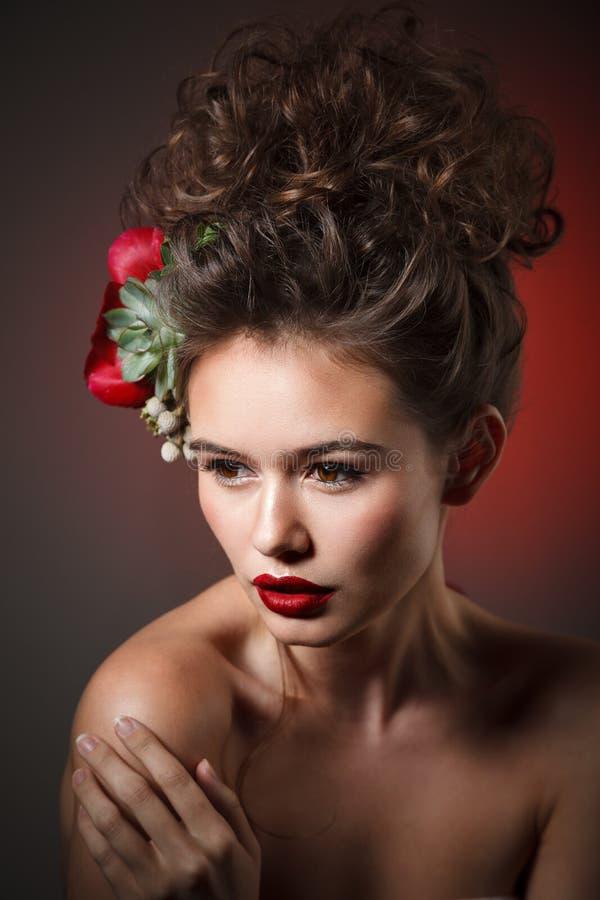 Retrato de la belleza de Stubio de la mujer joven atractiva con la peonía roja fotos de archivo