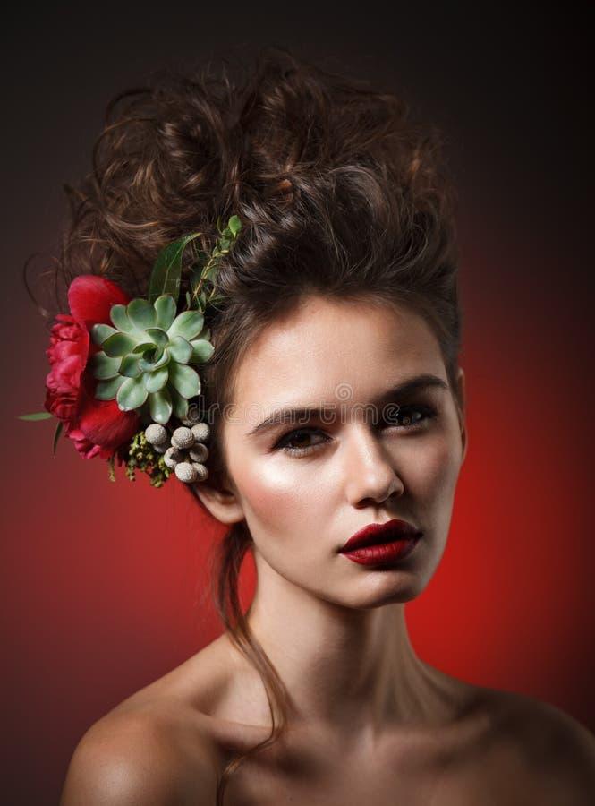 Retrato de la belleza de Stubio de la mujer joven atractiva con la peonía roja imágenes de archivo libres de regalías