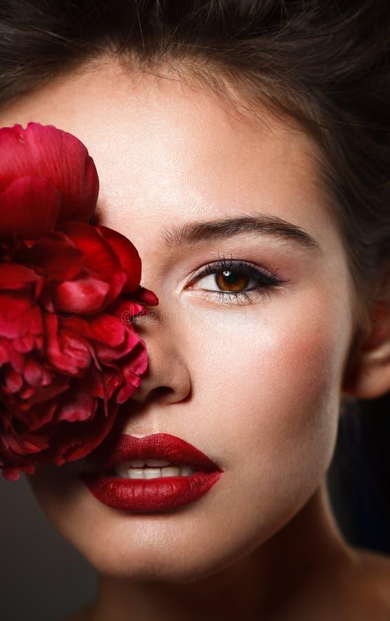 Retrato de la belleza de Stubio de la mujer joven atractiva con la peonía roja fotografía de archivo