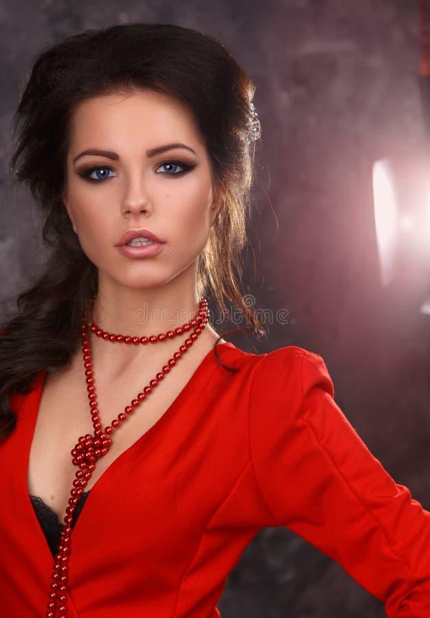 Retrato de la belleza de una morenita atractiva hermosa en un vestido rojo en un fondo gris fotografía de archivo libre de regalías