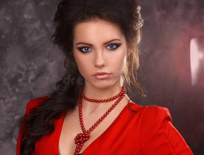 Retrato de la belleza de una morenita atractiva hermosa en un vestido rojo en un fondo gris fotos de archivo libres de regalías