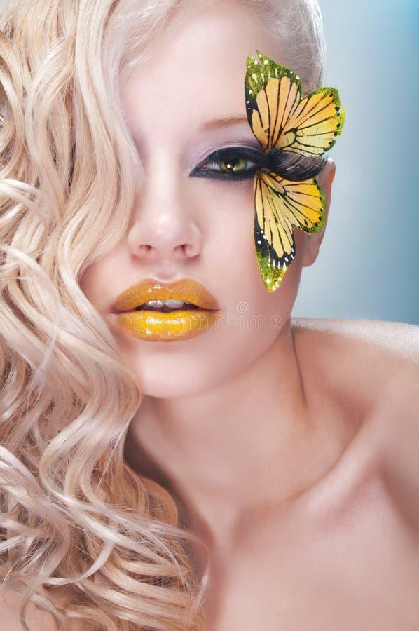 Retrato de la belleza del estudio con la mariposa amarilla fotografía de archivo