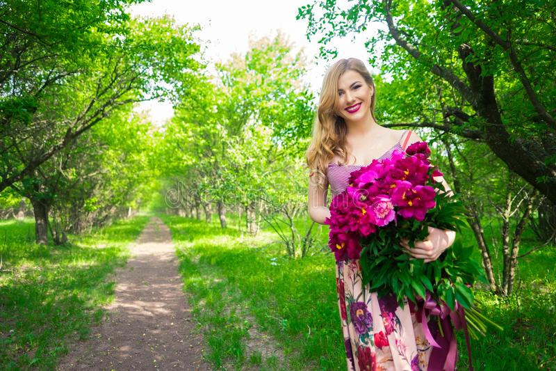 Retrato de la belleza del primer de la muchacha bonita joven con la peonía de la flor que lleva el lápiz labial rosado brillante, fotos de archivo libres de regalías