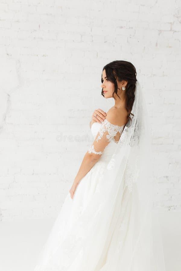 Retrato de la belleza del vestido de boda de la moda de la novia que lleva con las plumas con el maquillaje y el peinado de lujo, imágenes de archivo libres de regalías