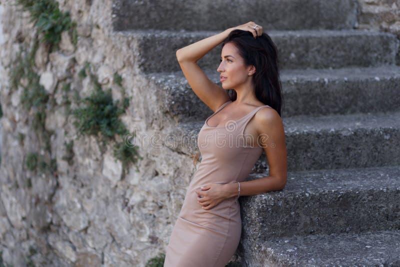 Retrato de la belleza en perfil de una muchacha morena caliente, atractiva, presentando cerca de las escaleras viejas hechas de p imagenes de archivo