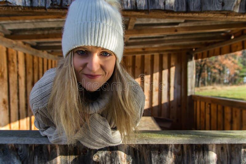 Retrato de la belleza joven en el casquillo blanco que mira del edificio de madera fotografía de archivo libre de regalías