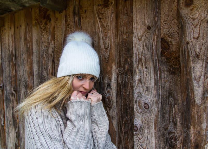 Retrato de la belleza joven en el casquillo y el suéter blancos con el fondo de madera foto de archivo libre de regalías