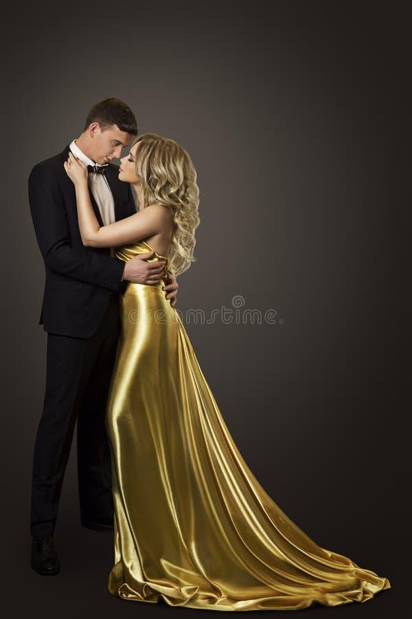 Retrato de la belleza de los pares de la moda, besando el hombre y a la mujer, vestido del oro fotografía de archivo libre de regalías