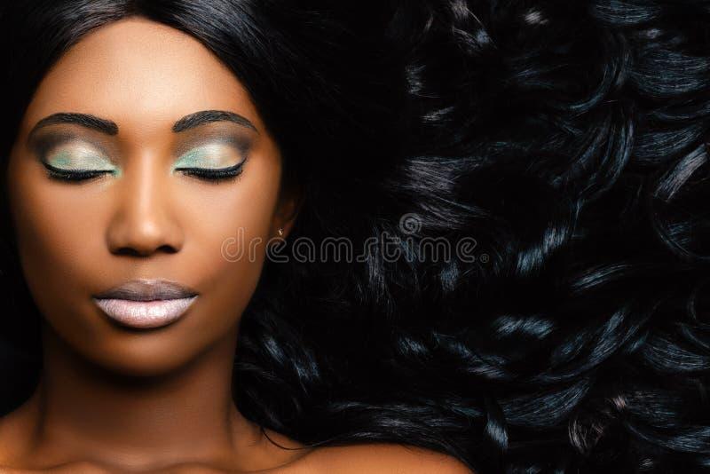 Retrato de la belleza de la mujer africana que muestra el pelo largo con las ondas lisas fotos de archivo