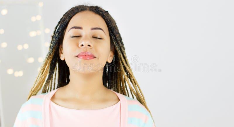 Retrato de la belleza de la mujer afroamericana con el peinado afro con los ojos cercanos y el maquillaje del encanto fotografía de archivo