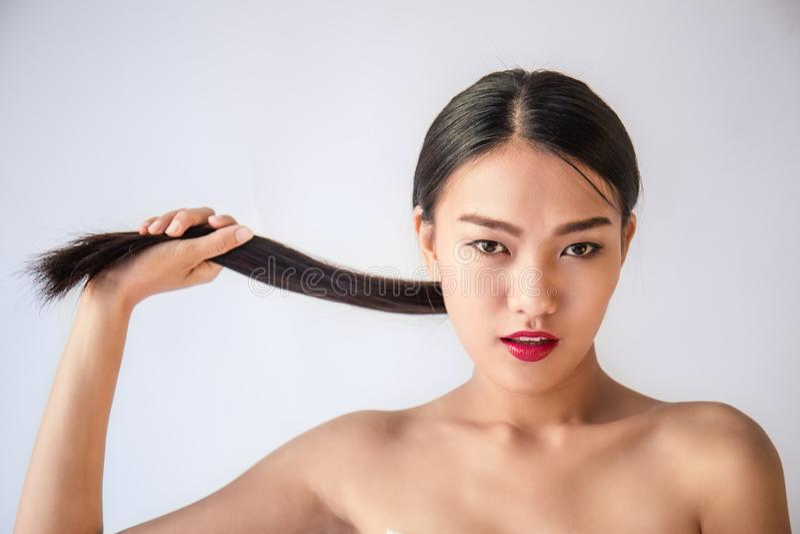 Retrato de la belleza de la mujer asiática joven con su mano que tira de su pelo negro largo fotografía de archivo libre de regalías