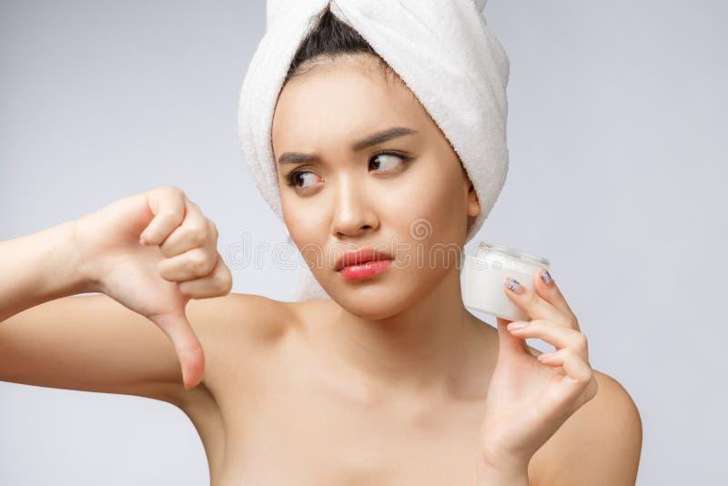 Retrato de la belleza de la mujer asiática semidesnuda que mira en cámara y que sostiene la crema de cara en su palma aislada sob imagen de archivo libre de regalías