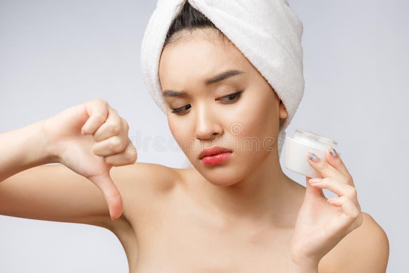 Retrato de la belleza de la mujer asiática semidesnuda que mira en cámara y que sostiene la crema de cara en su palma aislada sob imágenes de archivo libres de regalías