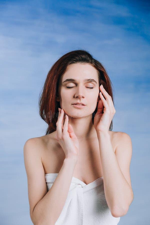 Retrato de la belleza de la mujer blanca joven tranquila que lleva a cabo las manos cerca de cara: únicos labios imágenes de archivo libres de regalías