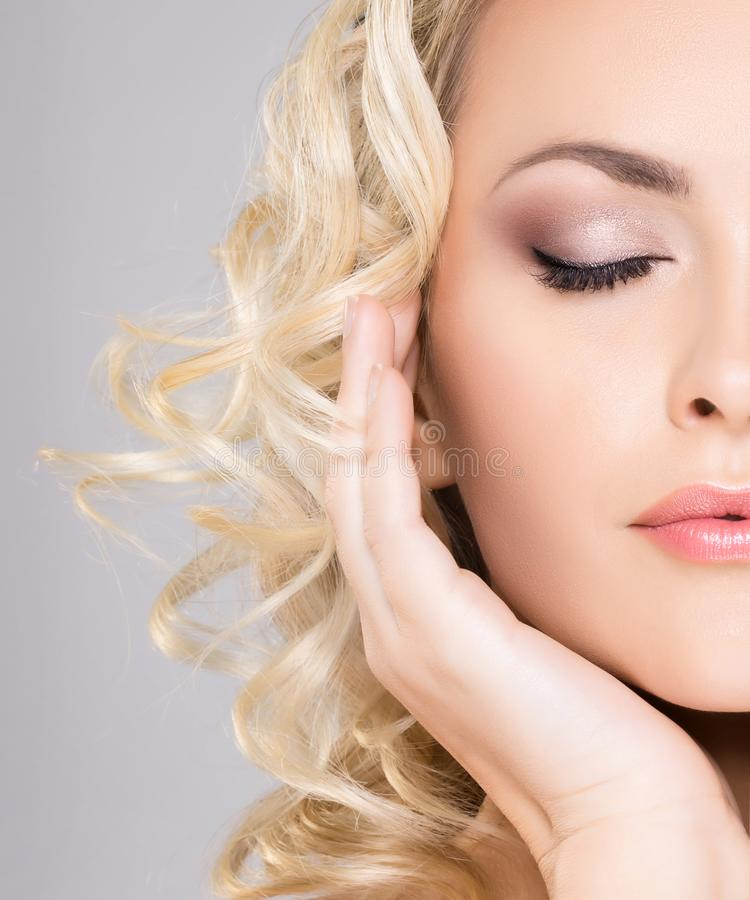 Retrato de la belleza de la mujer rubia atractiva con el pelo rizado y un peinado hermoso Maquillaje y concepto de los cosméticos fotografía de archivo