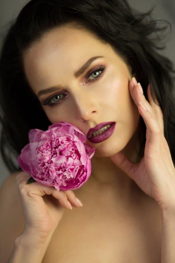 Retrato de la belleza de la señora morena hermosa con el flowe rosado de la peonía imágenes de archivo libres de regalías