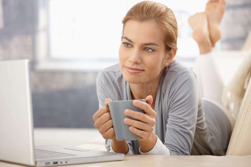 Retrato de la belleza soñadora con la computadora portátil y el café fotos de archivo