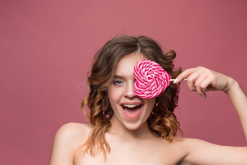 Retrato de la belleza de una muchacha linda en el acto para comer un caramelo imagen de archivo