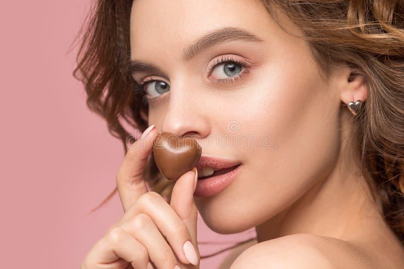 Retrato de la belleza de una muchacha linda en el acto para comer un caramelo de chocolate fotos de archivo libres de regalías