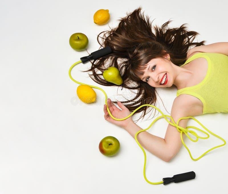Retrato de la belleza de una mujer rodeada por las frutas y de una cuerda que salta que miente en el piso imagenes de archivo