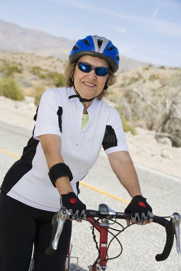 Retrato de la bicicleta que hace una pausa de la mujer mayor imagenes de archivo