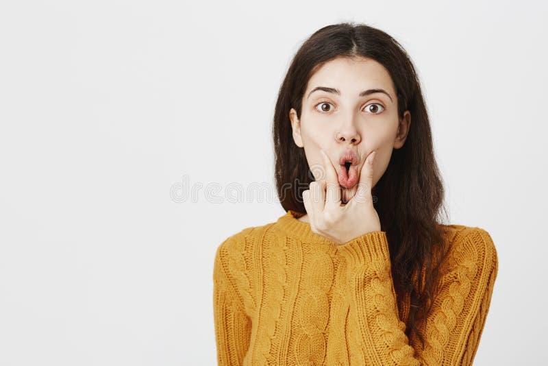 Retrato de la boca abierta que exprime femenina europea atractiva divertida y de mirar fijamente la cámara con mirada impresionad fotografía de archivo libre de regalías