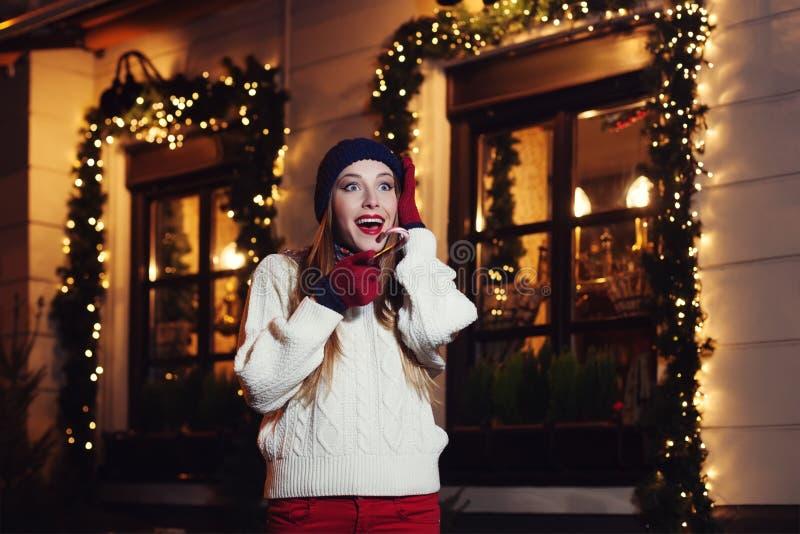 Retrato de la calle de la noche de la mujer hermosa joven que actúa ropa hecha punto elegante emocionada, que lleva Alegría de ex imagenes de archivo