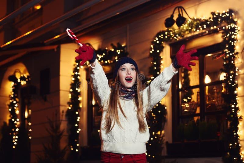 Retrato de la calle de la noche de la mujer hermosa joven que actúa ropa hecha punto elegante emocionada, que lleva Alegría de ex foto de archivo libre de regalías