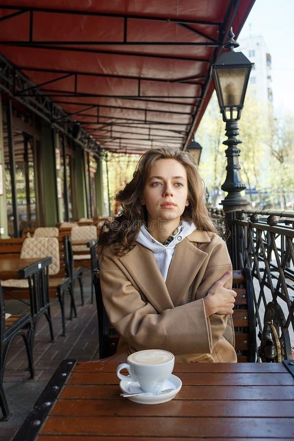Retrato de la calle de la mujer joven que lleva el caf? de consumici?n de la capa beige en el mirador del caf? con mirada so?ador foto de archivo libre de regalías