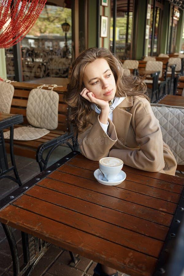 Retrato de la calle de la mujer joven que lleva el caf? de consumici?n de la capa beige en el mirador del caf? con mirada so?ador imagen de archivo libre de regalías