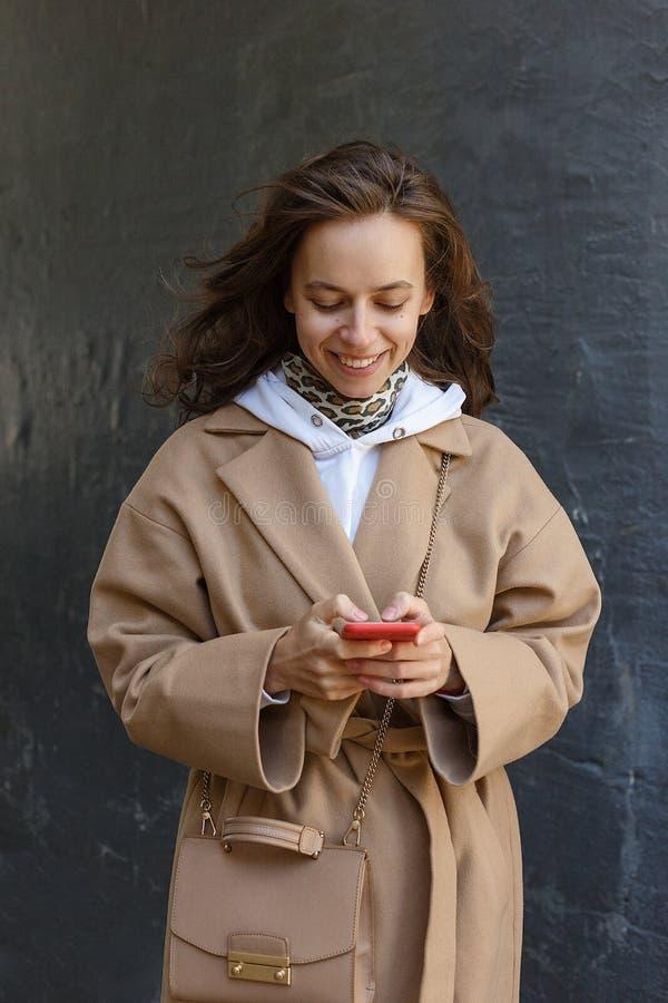 Retrato de la calle de la mujer sonriente joven que lleva la capa beige usando su teléfono elegante al aire libre Comunicación mo imagen de archivo