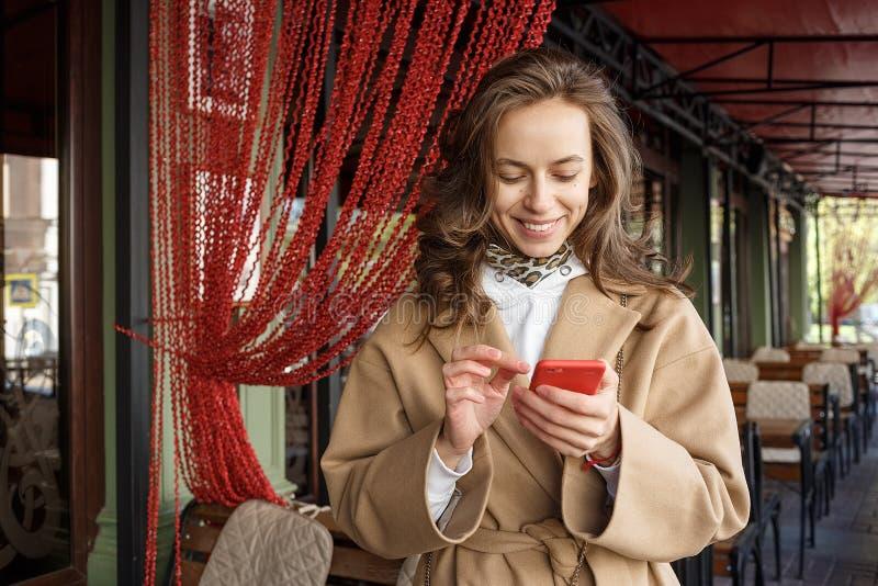 Retrato de la calle de la mujer sonriente joven que lleva la capa beige usando su teléfono elegante en un mirador del café fotos de archivo libres de regalías