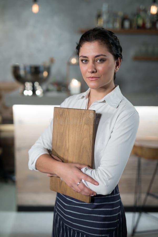 Retrato de la camarera confiada que lleva a cabo al tablero de madera fotografía de archivo