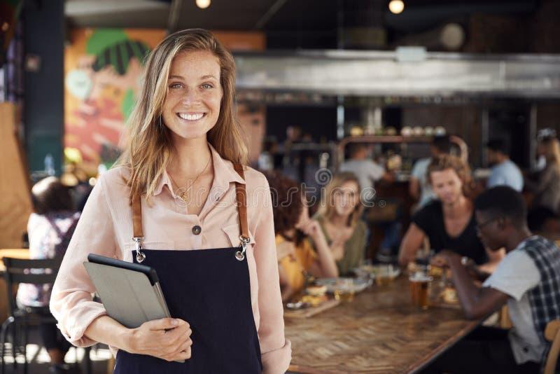 Retrato de la camarera Holding Menus Serving en restaurante ocupado de la barra imagenes de archivo