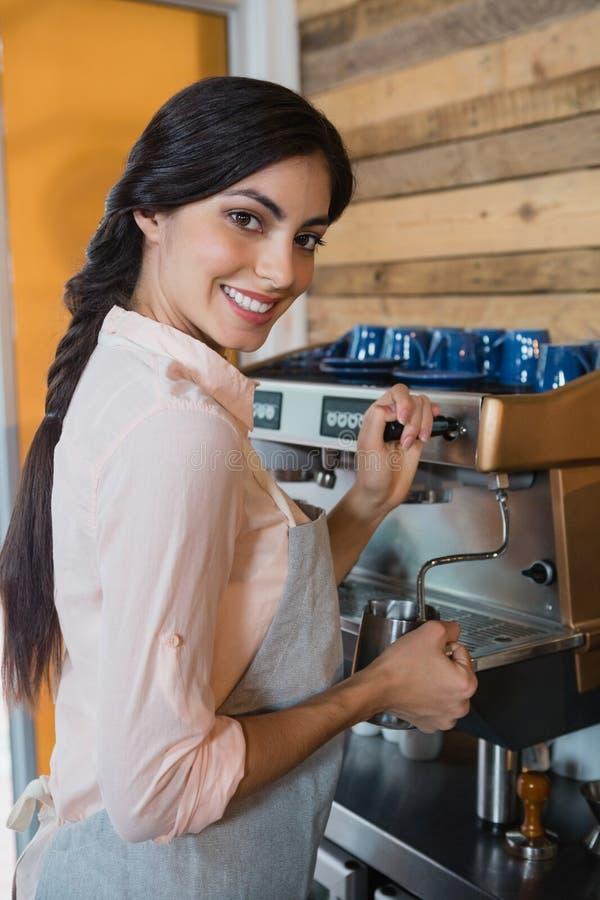 Retrato de la camarera que usa la cafetera fotografía de archivo libre de regalías