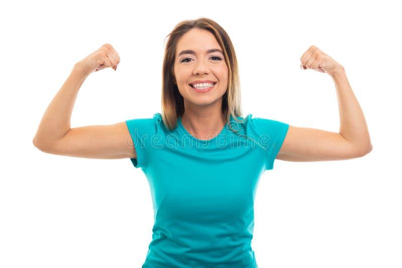 Retrato de la camiseta que lleva de la muchacha bonita joven que dobla ges del bíceps imagen de archivo libre de regalías